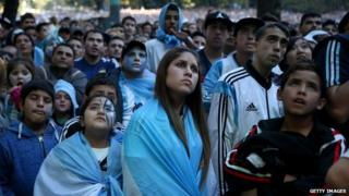 Argentine soccer fans watch a broadcast of their team playing Germany on a large screen setup in Plaza San Martin during the World Cup final in Buenos Aires, Argentina, 13 July 2014