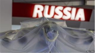 A model aircraft sits under plastic sheeting at Farnborough in front of a Russia sign