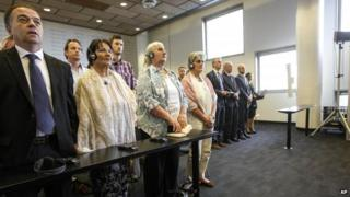 Women from the Bosnian town of Srebrenica stand as judges enter a civil court in The Hague, Netherlands, on Wednesday 16 July 2014