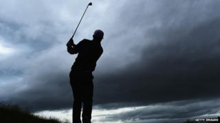 Silhouette of golfer Justin Rose swinging his club
