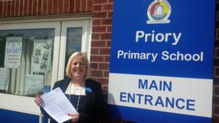 Headteacher Jill Bennett outside the school with the latest Ofsted report
