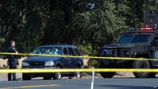 A Stockton Police officer investigated the scene after a vehicle involved in a suspected bank robbery in Stockton, California, on 16 July 2014