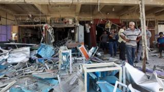 Civilians inspect the site of a bomb attack in the Jihad neighbourhood in Baghdad, 19 July 2014