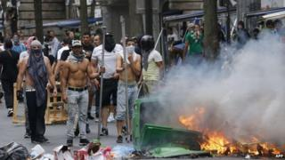 Protesters stand in front of burning bin near the aerial metro station of Barbes-Rochechouart, in Paris, 19 July 2014