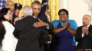 President Barack Obama is hugged after signing an executive order barring federal contractors from discriminating against gay and transgender workers (21 July 2014)
