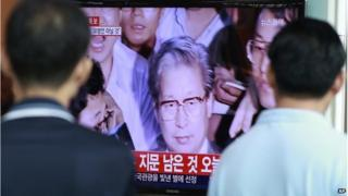 People watch TV news showing Yoo Byung-eun, the fugitive owner of the sunken ferry Sewol, at Seoul Railway Station in Seoul, South Korea, Tuesday, 22 July 2014.