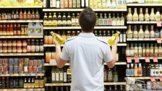 A man stares at shelves in a grocery store.