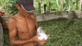 Colombian peasant holds bag of cocaine