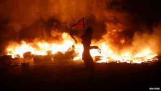 A Palestinian protester carried a flag past burning tyres at Qalandia, on the West Bank, 24 July 2014