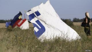 A woman takes a photograph of wreckage at the crash site of Malaysia Airlines Flight MH17 near the village of Hrabove (Grabovo), Donetsk region on 26 July 2014.
