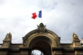 The French flag flies at half-mast above the entrance of the Elysee Palace in Paris - 28 July 2014