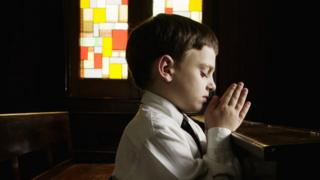 A boy prays in a church.