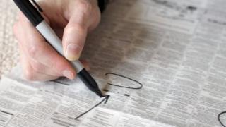 Circling jobs in newspaper