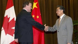 Canada's Foreign Minister John Baird, left, shakes hands with Chinese Foreign Minister Wang Yi before a meeting at the Foreign Ministry in Beijing, China, 29 July 2014