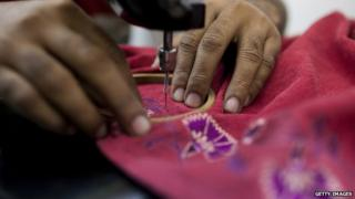 Hands of an Indian woman using a sewing machine