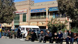 This picture taken on 8 November 2013 shows a group of Uighur men sitting by a street in Kashgar, farwest China's Xinjiang region.