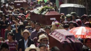 Relatives carry coffins of some of the 31 villagers massacred during the civil war in 1982, in Santa Maria Nebaj, Guatemala, 30 July 2014