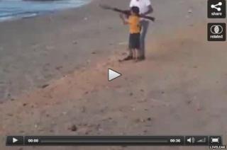Young boy firing a rocket propelled grenade on a beach