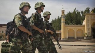 Chinese soldiers march in front of China's largest mosque in the city of Kashgar in Xinjiang - 31 July 2014