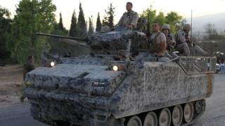 A Lebanese army's armoured personal carrier (APC) drives to the entrance of the town of Arsal in the Bekaa valley by the Syrian border on 2 August 2014