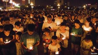 Residents gather as they attend a candlelight vigil for victims of a factory explosion, in Kunshan, Jiangsu province 2 August 2014
