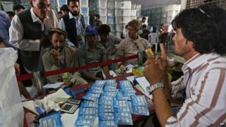 Afghan election commission workers sort ballot papers for an audit of the presidential run-off votes at an election commission office in Kabul, Afghanistan, Sunday, Aug. 3, 2014