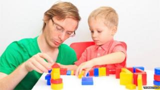 Father and son play with colourful block