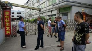 Debt collectors outside Dongguan Shinyang Electronics factory