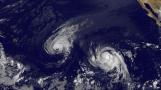 This image provided by NOAA shows Hurricane Iselle, center, and tropical storm Julio, right 6 August 2014