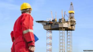 Worker standing in front of oil rig