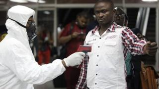 Nigerian port health official uses thermometer on worker at arrivals hall of airport in Lagos, Nigeria. 6 Aug 2014