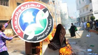 A man burns the logo of the Freedom and Justice Party (FJP) in Cairo on 23 August 2013