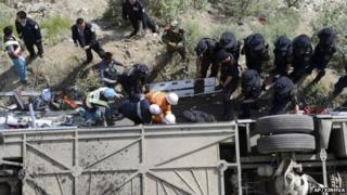 Rescuers try to pull out bodies and survivors from an overturned tour bus after it fell off a cliff in Nyemo County, Aug. 9
