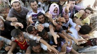 Displaced Iraqis from the Yazidi community gather for humanitarian aid at the Syria-Iraq border