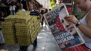 """A man reads a newspaper in central Istanbul, Turkey, with a front page headline reading """"President of the Nation"""""""