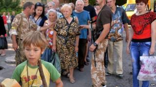 A young boy holds a loaf of bread as residents of the eastern Ukrainian city of Lysychansk queue to receive bread distributed as part of humanitarian aid on 27 July 2014.