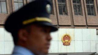 A policeman stands guard at the Shanghai Intermediate Court on 8 August, 2014