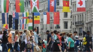 People crossing a London street with flags