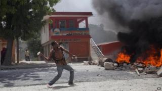 A supporter of Haiti's former President Jean-Bertrand Aristide throws rocks in Port-au-Prince, August 14, 2014.