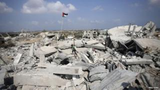 Palestinian flag over a destroyed house in Gaza, 17 August 2014