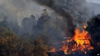 A structure burns along Highway 41 in Oakhurst, California 18 August 2014