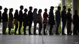 Silhouette of people waiting in a queue