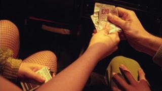 Man paying a woman