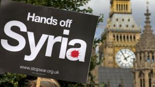 Demonstrators hold up placards during a protest against potential British military involvement in Syria at a gathering outside the Houses of Parliament