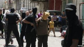 A Hamas militant grabs a Palestinian suspected of collaborating with Israel, before executing him in Gaza City