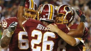 Washington Redskins tackle Tom Compton (68) and quarterback Kirk Cousins (8) celebrate with running back Evan Royster (26), after Royster's touchdown during the first half of an NFL preseason football game 18 August 2014