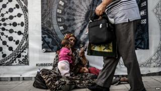 A woman and child begging on a street in Istanbul (July 2014)