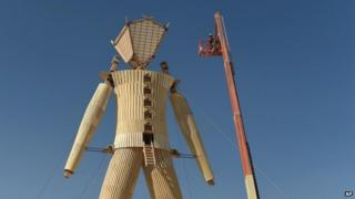 """Artists and volunteers work on the """"Man"""" at the annual Burning Man event on the Black Rock Desert of Gerlach, Nevada 24 August 2014"""