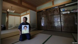 Mikio Watanabe holds a portrait of his late wife Hamako at his home at Yamakiya district in Kawamata town, Fukushima prefecture in this 23 June 2014 file photo