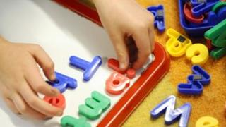 Primary pupil playing with letters